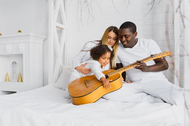 ギターが付いているベッドで幸せな家族