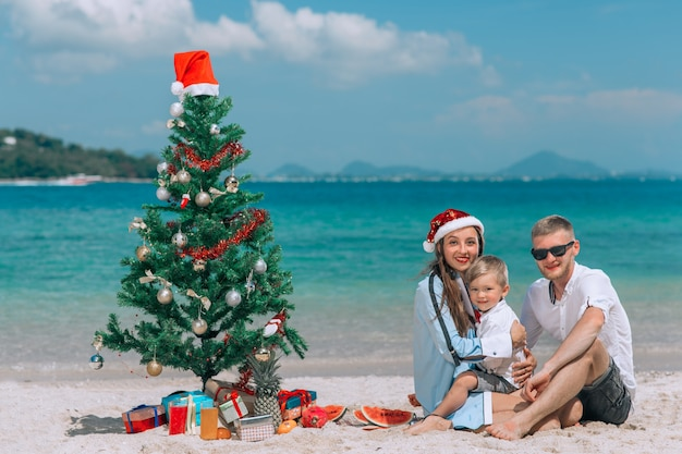 白いビーチで楽しんでいるクリスマス帽子の幸せな家族