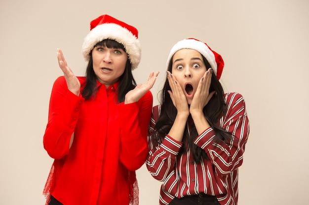 クリスマスセーターポーズで幸せな家族。愛の抱擁、休日の人々を楽しんでいます。スタジオで灰色の背景にママと娘