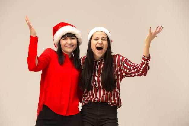 Счастливая семья в представлять свитер рождества. наслаждаюсь любовными объятиями, праздниками людей. мама и дочь на сером фоне в студии