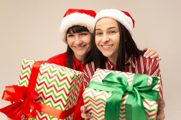 贈り物でポーズをとるクリスマスセーターの幸せな家族。愛の抱擁、休日の人々を楽しんでいます。スタジオで灰色の背景にママと娘