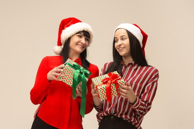贈り物でポーズをとってクリスマスセーターの幸せな家族
