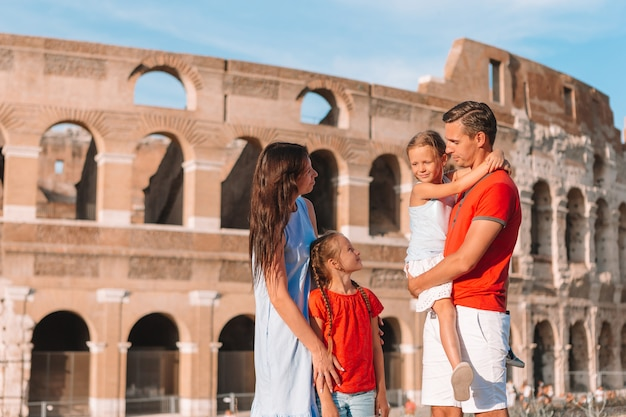 Счастливая семья в европе. родители и дети в риме над колизеем