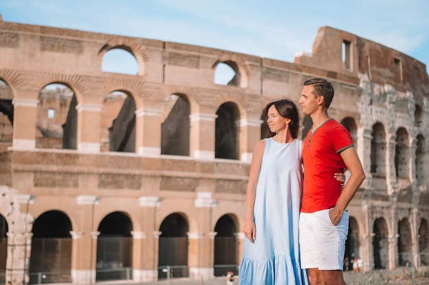 Счастливая семья в европе. романтическая пара в риме над колизеем