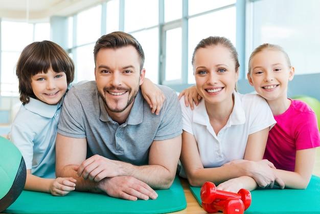 フィットネスクラブで幸せな家族。一緒にエクササイズマットの上に横たわっている間互いに結合する幸せなスポーティーな家族