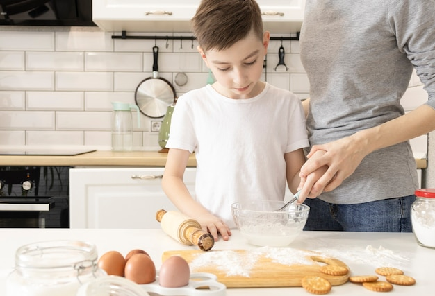 キッチンで幸せな家族。母と子が生地を準備し、クッキーを焼く