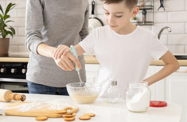 부엌에서 행복 한 가족입니다. 반죽, 구워 쿠키를 준비하는 엄마와 아이