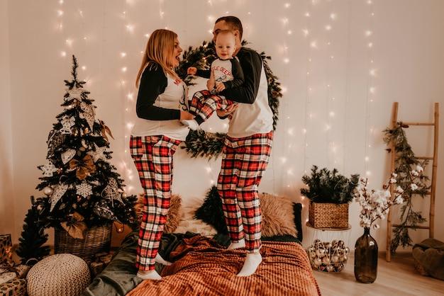 子供親とパジャマを着た幸せな家族は、寝室のベッドでジャンプする子供と遊ぶ。新年の家族の服は衣装に見えます。バレンタインデーのお祝いの贈り物