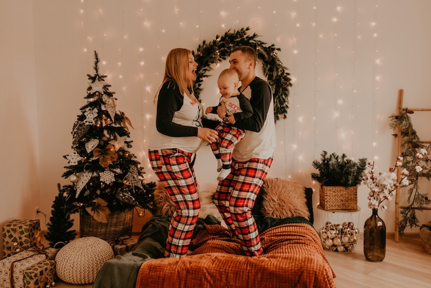 Счастливая семья в пижаме с детьми и родителями играет с ребенком, прыгающим на кровати в спальне. новогодняя семейная одежда смотрится нарядами. подарки на день святого валентина