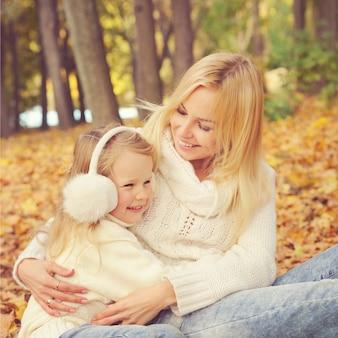 Счастливая семья в парке, улыбающаяся мать и маленькая дочь отдыхают в осеннем парке