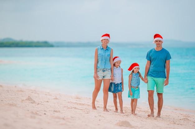 クリスマス休暇を祝う熱帯のビーチで赤いサンタ帽子の幸せな家族