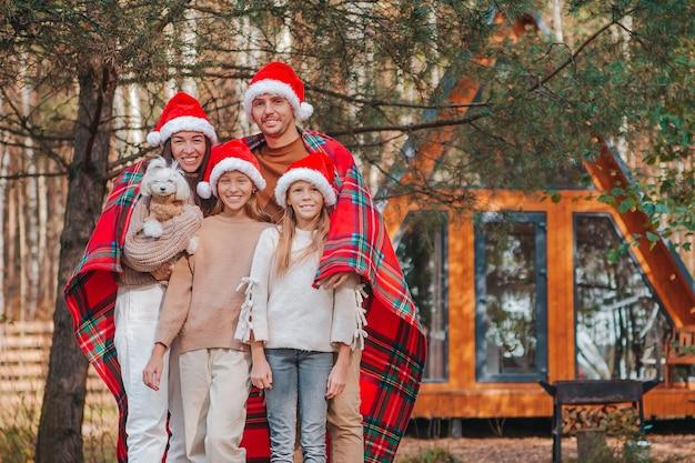 Счастливая семья в шляпе санта, наслаждаясь рождественскими каникулами