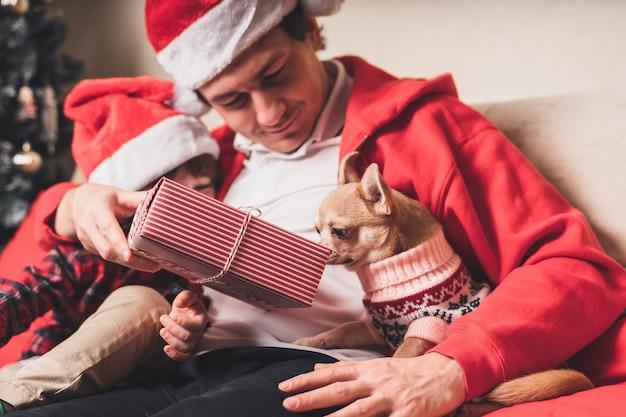 Счастливая семья в шляпе санта-клауса, отец и ребенок сын делают рождественский подарок дома