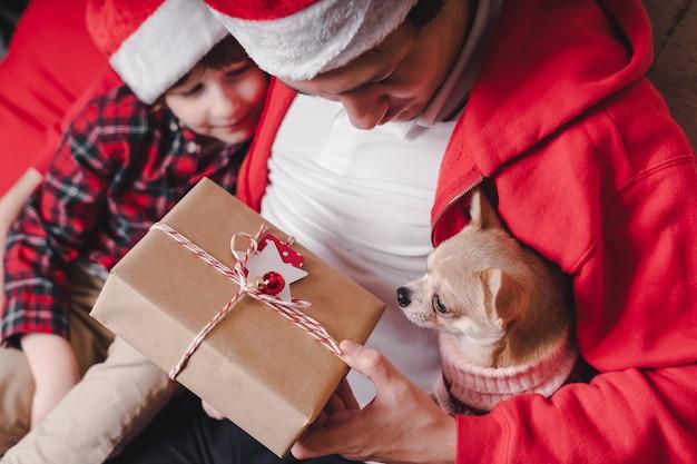 Счастливая семья в новогодней шапке с собакой в рождественском свитере