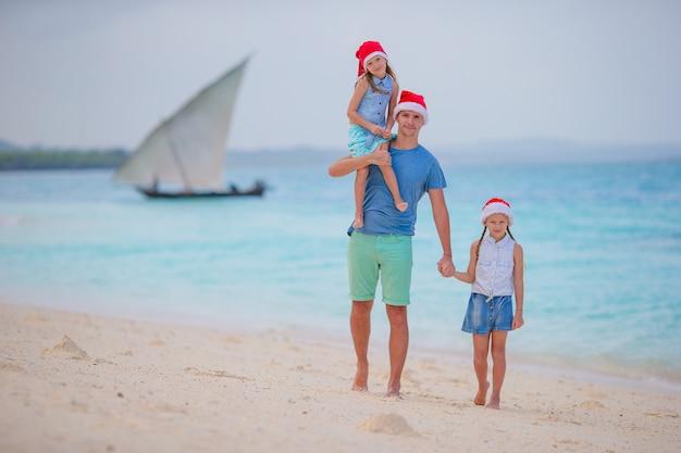 여름 휴가에 산타 모자에 행복 한 가족. 바다 여행을 즐기는 4 명의 젊은 가족과 함께 크리스마스 휴가