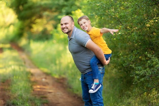 Счастливая семья летом: сын сидит на спине отца.