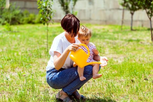 庭で幸せな家族。じょうろからの水が子供の手に注がれます。母は黄色いじょうろから庭の子供に手を洗います。