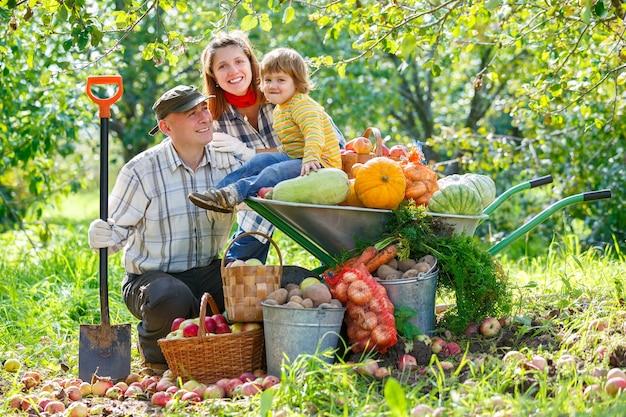 Счастливая семья в саду с урожаем овощей и фруктов