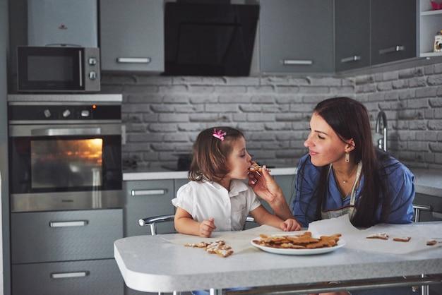 台所で幸せな家族。休日の食品のコンセプト。母と娘はクッキーを飾ります。自家製ペストリーを作るのに幸せな家族。自家製料理と小さなヘルパー