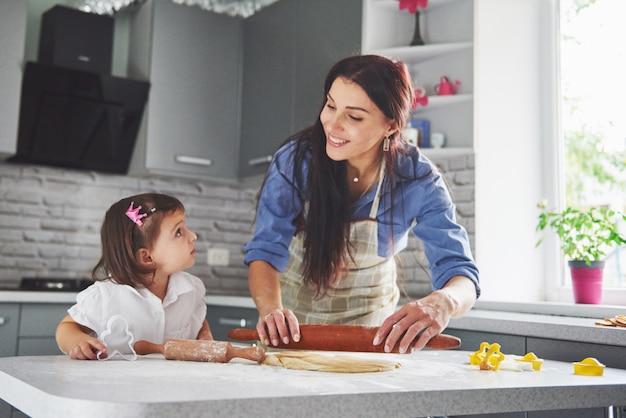 台所で幸せな家族。休日の食品のコンセプト。母と娘が生地を準備して、クッキーを焼きます。家でクッキーを作るのに幸せな家族。自家製料理と小さなヘルパー