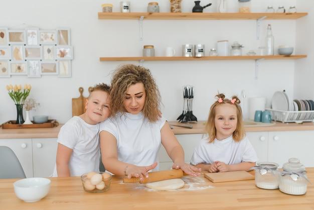 キッチンで幸せな家族。生地を準備する母と子、クッキーを焼く