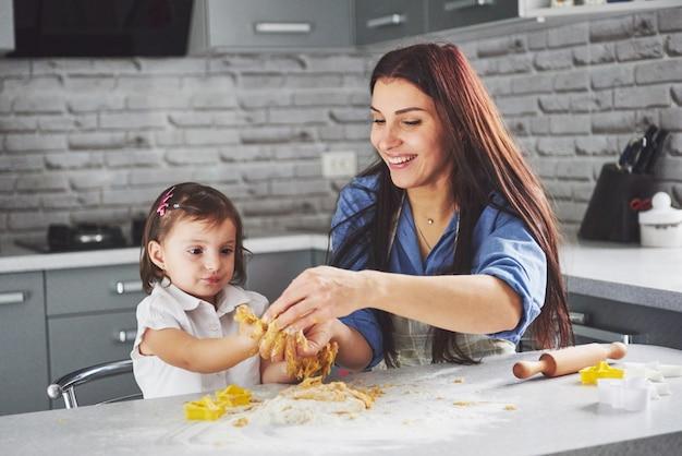 台所で幸せな家族。母と娘が生地を準備して、クッキーを焼きます。
