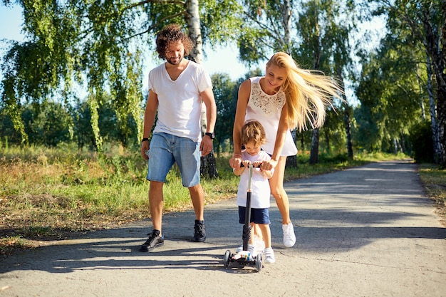 公園で幸せな家族。スクーターに子供を持つ親は自然の中を歩いています。
