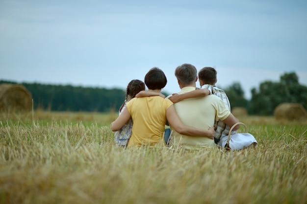 晴れた日の麦畑で幸せな家族、背面図