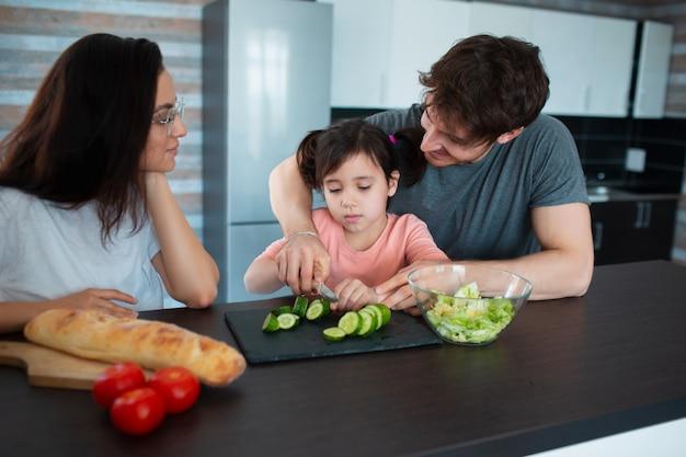 Счастливая семья готовит на кухне. отец учит дочь нарезать овощи. мама смотрит на них