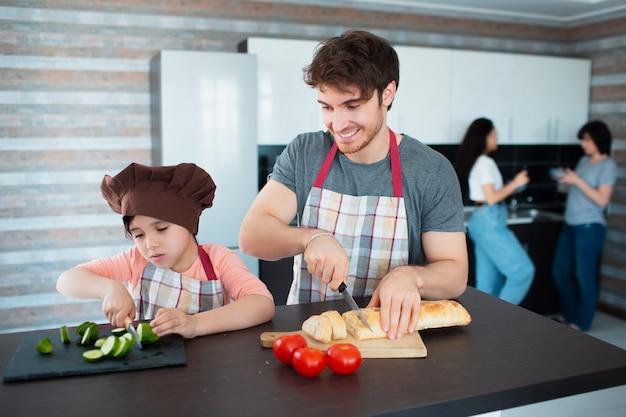 幸せな家族が台所で料理をしています。父は娘に野菜を切るように教えます。
