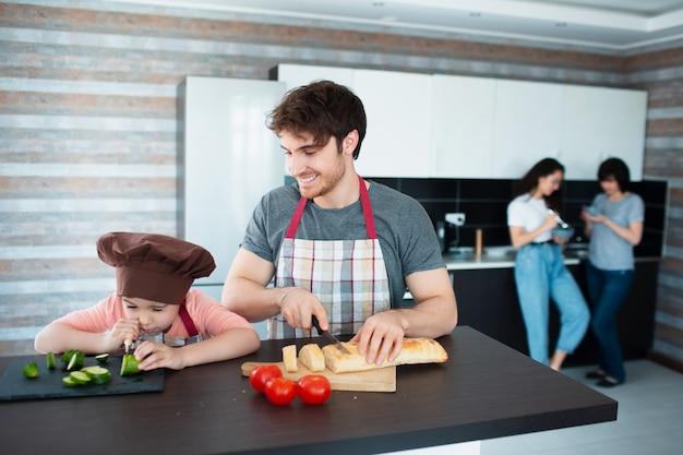 Счастливая семья готовит на кухне. отец учит дочь нарезать овощи.