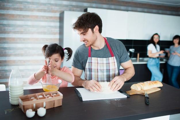 幸せな家族が台所で料理をしています。父は娘に野菜を切るように教えます。 。