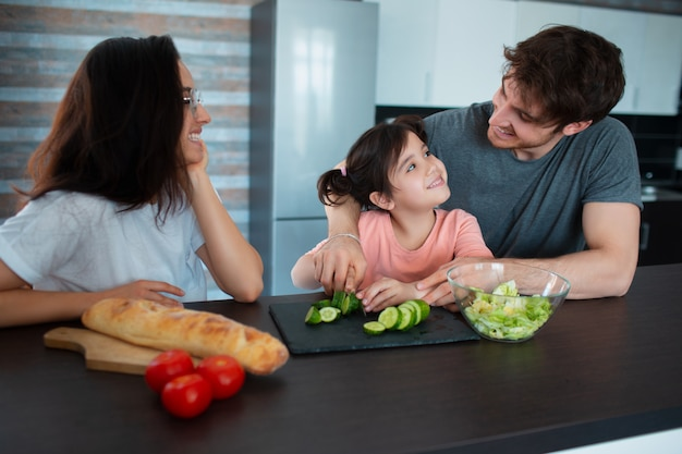 Happy family is cooking in the kitchen. father teaches daughter to cut vegetables. mother looks at them