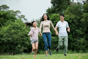 Happy family is having fun Mother, father and daughter are running in park.