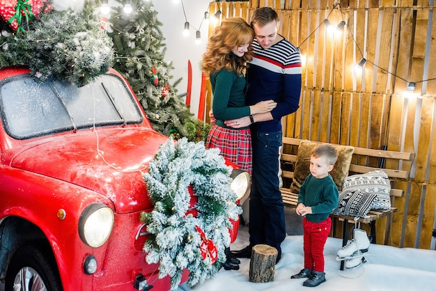 A happy family is having fun, playing with little son near a red car with gifts, christmas  trees
