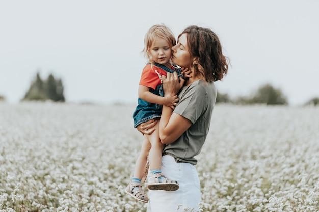 Счастливая семья играет, веселится на поле с цветами на закате.