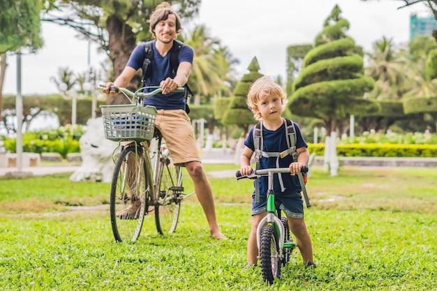 Счастливая семья катается на велосипедах на открытом воздухе и улыбается отец
