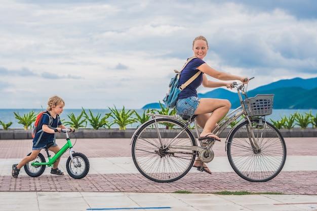 Счастливая семья катается на велосипедах на открытом воздухе и улыбается. мама на велосипеде, а сын на беговеле.