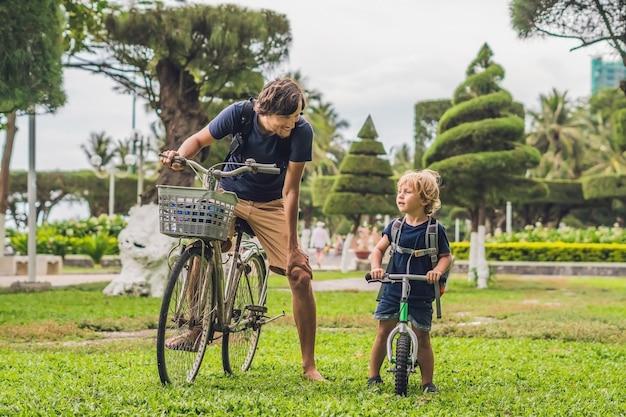 幸せな家族は屋外で自転車に乗って笑っています