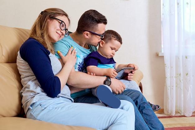 행복한 가족은 소파에 방에 태블릿과 함께 앉아있다