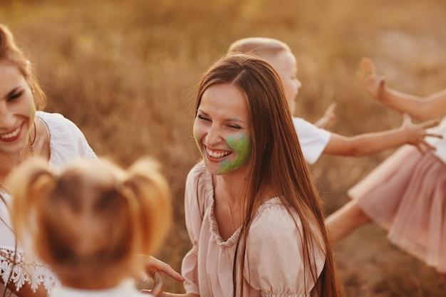 Счастливая семья измазана краской. дети играют с красками фестиваля холи. концепция индийского фестиваля холи. национальный, семейный праздник, выборочный фокус