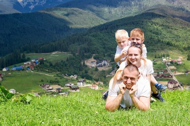 Счастливая семья: радостные отец, мать и двое сыновей лежат на зеленой траве на фоне леса, гор и неба с облаками.