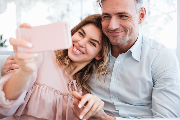 Happy family of joyful married couple making selfie and having great time together, while dating in city cafe