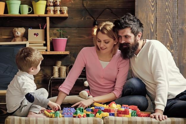 おもちゃで遊ぶ幸せな家族の子供たち父母とかわいい息子は親の概念を気遣うコンストラクターレンガで遊ぶ