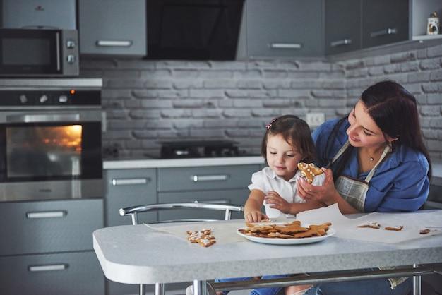 Famiglia felice in cucina. concetto di cibo per le vacanze. la madre e la figlia decorano i biscotti. famiglia felice nella produzione di pasticceria fatta in casa. cibo fatto in casa e piccolo aiuto