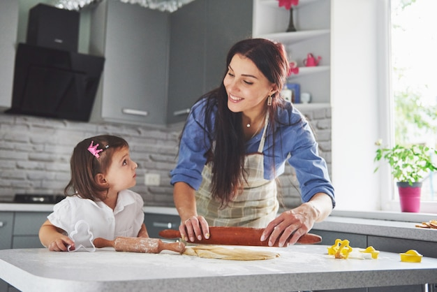 Happy family in the kitchen. holiday food concept. mother and daughter preparing the dough, bake cookies. happy family in making cookies at home. homemade food and little helper