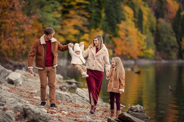 Happy family on the lake in the mountains for a walk in the fall