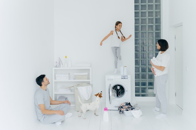 Happy family do laundry at home, father sits on floor in lotus pose, mother stands with white towel, look at child who dances happily on washing machine, pedigree dog near. household chores.