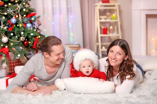 Happy family laying on the floor in the decorated christmas room