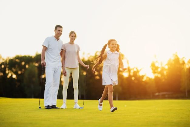 Happy family leisure golfers walk by fairway.